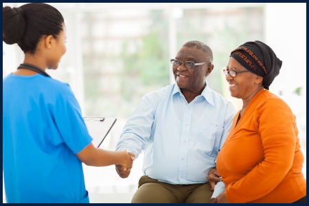 22062889 - friendly african female nurse greeting senior couple in hospital