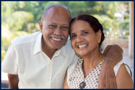 50717987 - closeup portrait, retired couple in white shirt and dress holding each other smiling,enjoying life together, isolated outside green trees background.