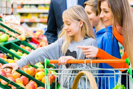 27447133 - family in supermarket selecting fruits while grocery shopping